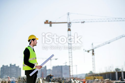 1041465228 istock photo Professional engineer architect worker with protective helmet and blueprints paper construction site 1183769757