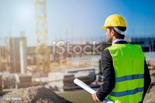 1041465228 istock photo Professional engineer architect worker with protective helmet and blueprints paper construction site 1183769934
