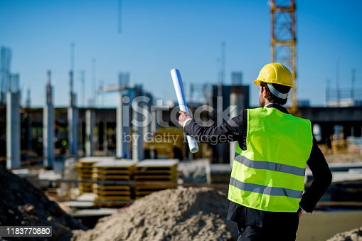1041465228 istock photo Professional engineer architect worker with protective helmet and blueprints paper construction site 1183770880