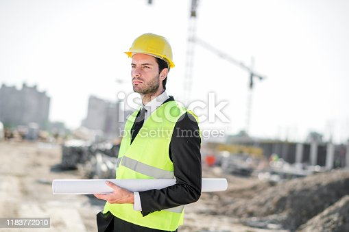 1041465228 istock photo Professional engineer architect worker with protective helmet and blueprints paper construction site 1183772010