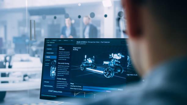professional engineer arbeitet an einem computer mit einer 3d-cad-software und testet den prototypen des elektroauto-chassis mit rädern, batterien und motor, die in einem high-tech-entwicklungslabor stehen. - prototype stock-fotos und bilder