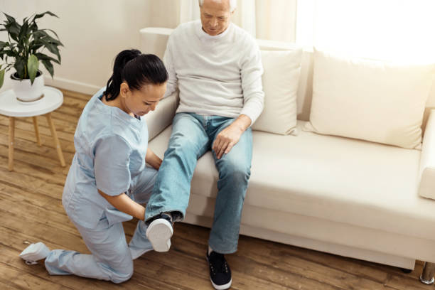 Professional experienced caregiver warming up her patients leg Special exercise. Pleasant professional experienced caregiver sitting on one knee and warming up her patients leg while doing special psychical exercises drug rehab stock pictures, royalty-free photos & images