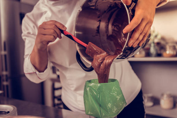 Professional experienced cook working in the bakery Best pastry. Professional experienced cook working in the bakery while preparing the best pastry icing bag stock pictures, royalty-free photos & images