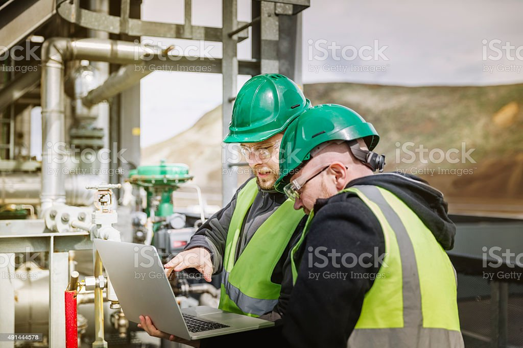 Professional experts discussing over laptop at factory stock photo