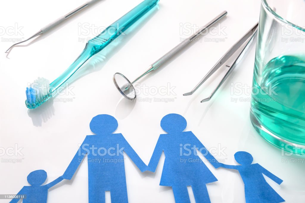 Professional family concept dentist with tools on white table elevated stock photo