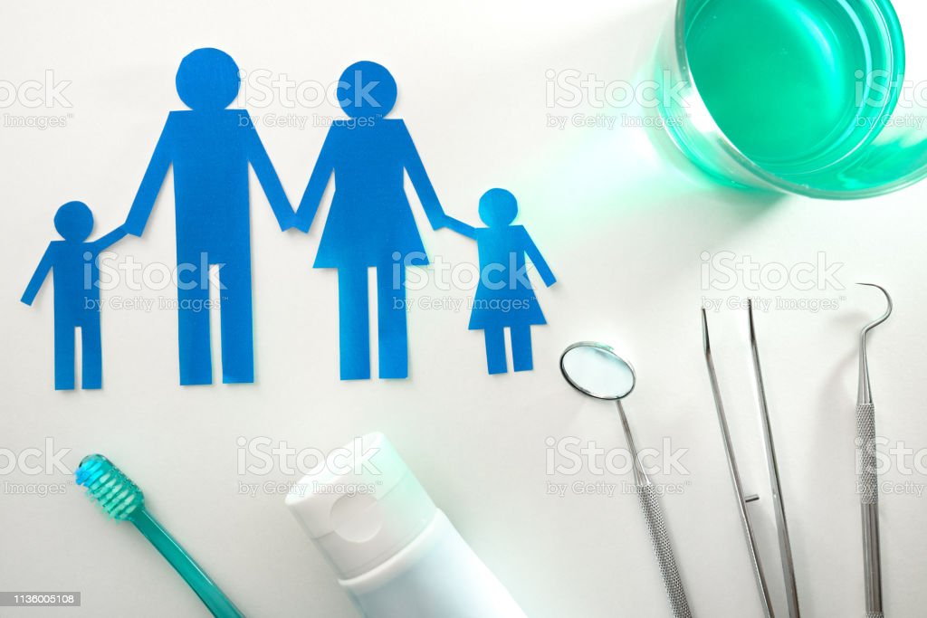 Professional family concept dentist with tools on white table top stock photo