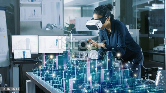 istock Professional Female Architect Wearing Makes Gestures with Augmented Reality Headset, Shows Statistics for 3D City Model. High Tech Office Use Virtual Reality Modeling Software Application. 921019714