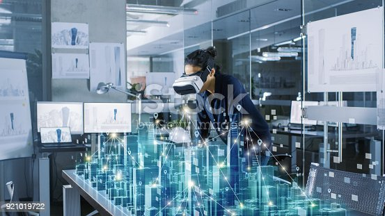 istock Professional Female Architect Wearing Makes Gestures with Augmented Reality Headset, Shows Statistics for 3D City Model. High Tech Office Use Virtual Reality Modeling Software Application. 921019722