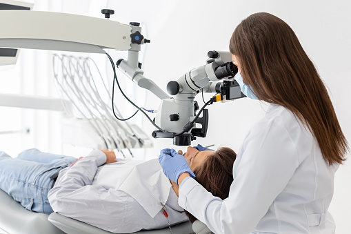 Professional female dentist using modern technologies in treatment