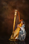 Professional female harpist during performance on stage, Hot colours on the background. Shot with D800, ISO 100, processed from RAW.