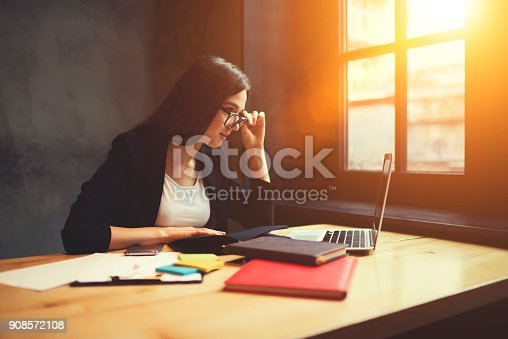 904263506 istock photo Professional female marketing expert in formal wear and glasses monitoring news 908572108