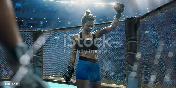 A close up composite image of a professional female mixed martial arts fighter dressed in tight shorts, sports bra, and grappling gloves. The fighter is wearing a mouth guard and raising her fist whilst screaming in victory. She stands in an octagon cage in a generic indoor sports arena.