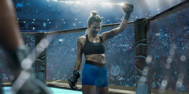 Professional Female Mixed Martial Arts Fighter Raising Fist In Victory stock photo