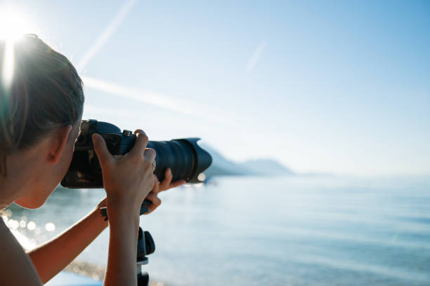 Professional female photographer taking photo of beautiful morning sea stock photo