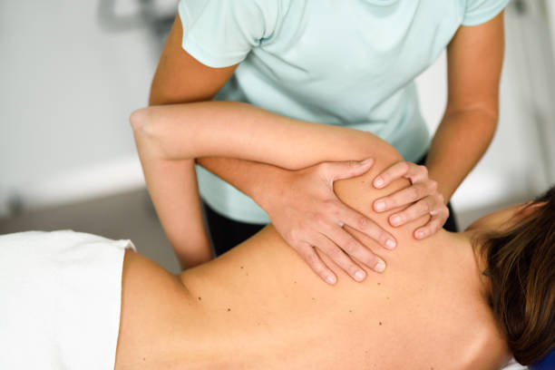 professional female physiotherapist giving shoulder massage to a woman - osteopathy stock pictures, royalty-free photos & images
