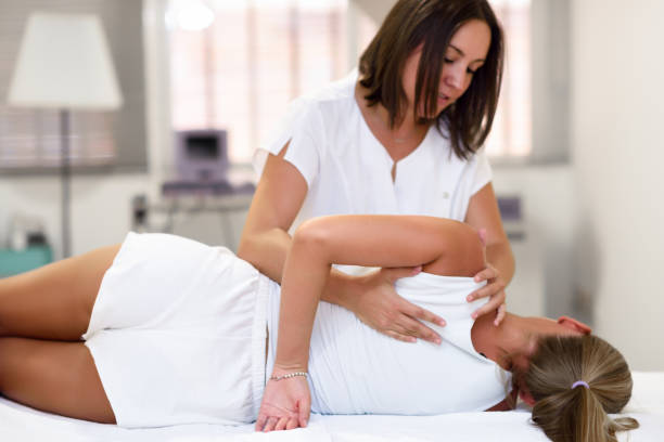 professional female physiotherapist giving shoulder massage to blonde woman - osteopathy stock pictures, royalty-free photos & images