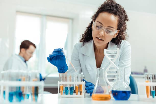 professional female scientist taking a vaccine sample - ricerca scientifica foto e immagini stock