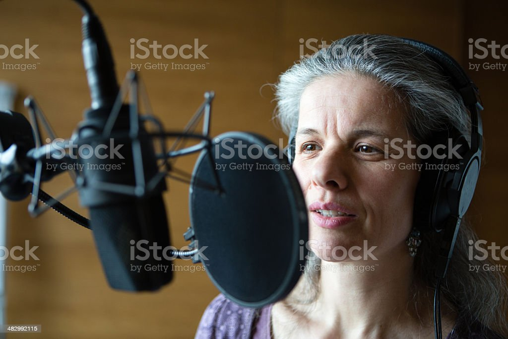 professional female speaker in the recording studio behind microphone royalty-free stock photo
