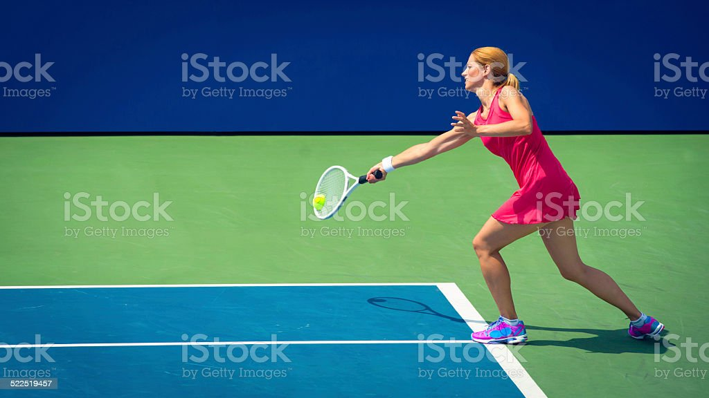 Professional Female Tennis Player Hitting a Forehand stock photo
