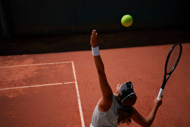 Professional female tennis player serving ball during match stock photo