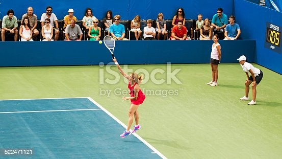 Professional fenake tennis player serving a ball on a tennis stadium, crowd in the background.