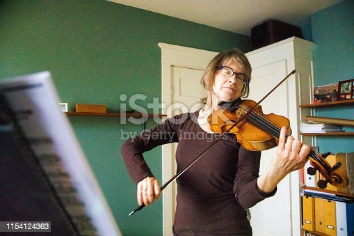 Professional female violinist rehearsing an emotional music piece at home, eyes closed, letting her musical expression be freed.