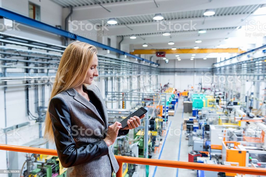 Professional female worker with tablet in futuristic factory - foto de acervo