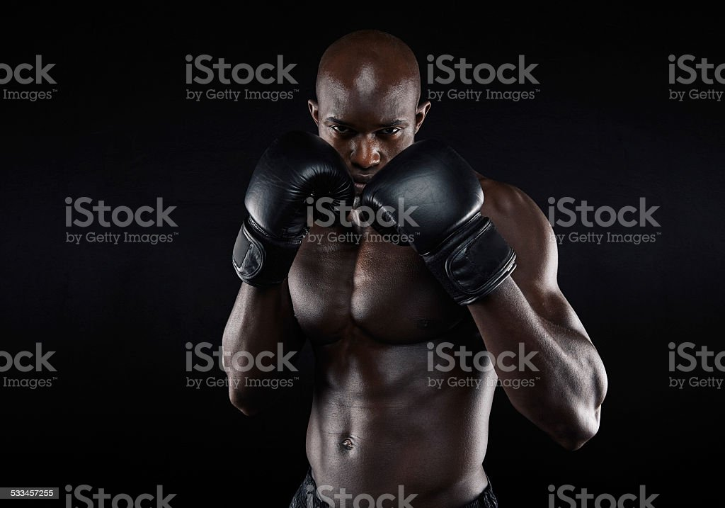 Portrait of tough male boxer posing in boxing stance against black...