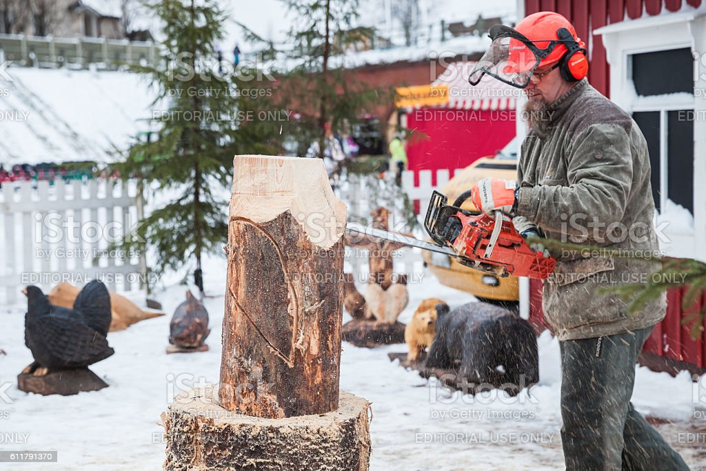 Professional Finnish sculptor with a chainsaw stock photo