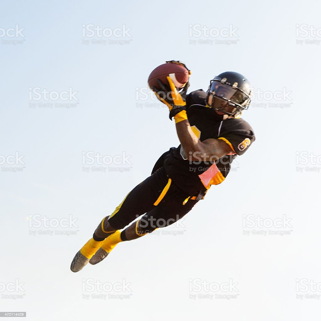 Professional football player jumping to catch ball during game stock photo