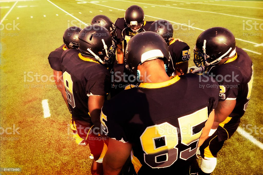 Professional Football Players Huddle on the Field stock photo