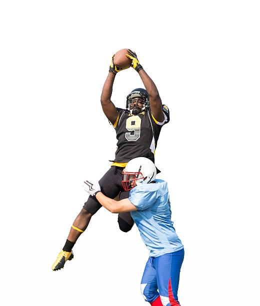 Professional Football Receiver Jumps Up to Catch the Ball A professional football receiver jumps up to catch a football while being tackled. wide receiver athlete stock pictures, royalty-free photos & images