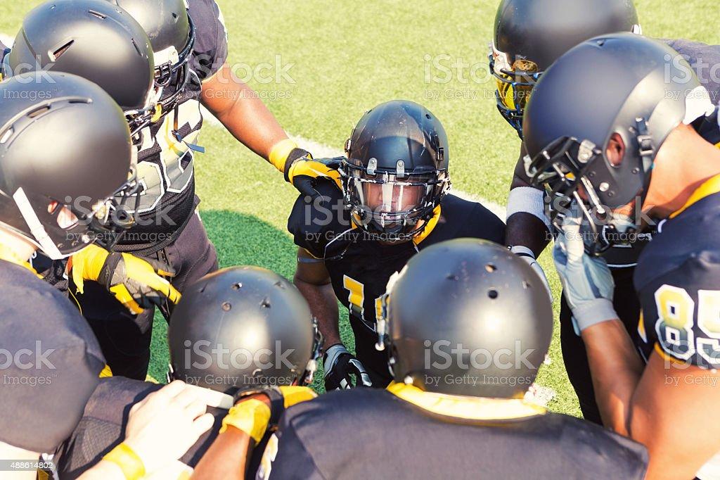 Professional football team talking in huddle on football field sidelines stock photo