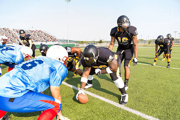 Professional football teams preparing for play during game at stadium Professional football teams preparing for play during game at stadium quarterback stock pictures, royalty-free photos & images