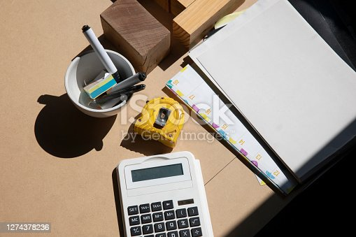Professional framers equipment on workbench including yellow tape measure, calculator, pens, pencils & note paper.