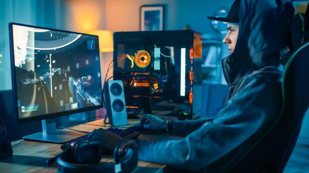 プロゲーマーとストリーマーは、彼のクールなパーソナルコンピュータ上で一人称シューティングゲームオンラインビデオゲームをプレイ。若い男は帽子とフードを着ている。部屋とpcはカ� - ゲーム ヘッドフォン ストックフォトと画像