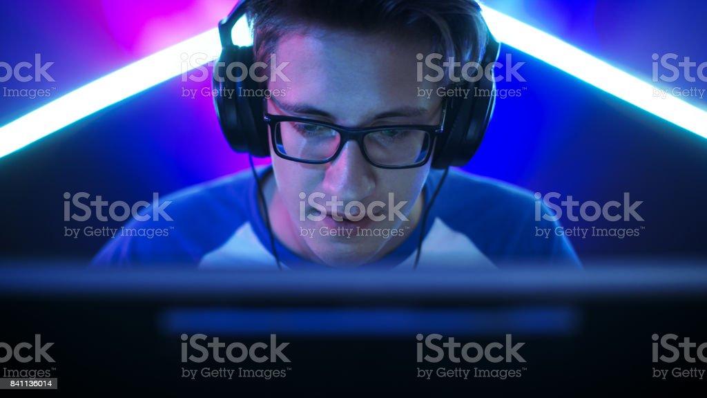 Juegos Gamer profesionales en MMORPG / estrategia / Shooter videojuegos en su computadora. Él participa en torneo de juegos en línea Cyber, juegos en casa o en café Internet. Lleva gafas y auriculares, de juegos de azar habla por micrófono. foto de stock libre de derechos