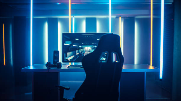 Professional Gamers Room With Ultra Powerful Personal Computer. Paused First-Person Shooter Game on Screen. Room Lit by Neon Lights in Retro Arcade Style. Cyber Sport Championship. stock photo