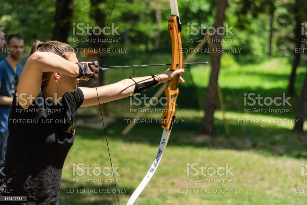 Professional girl archer with bow shoot arrow in the forest on knight...