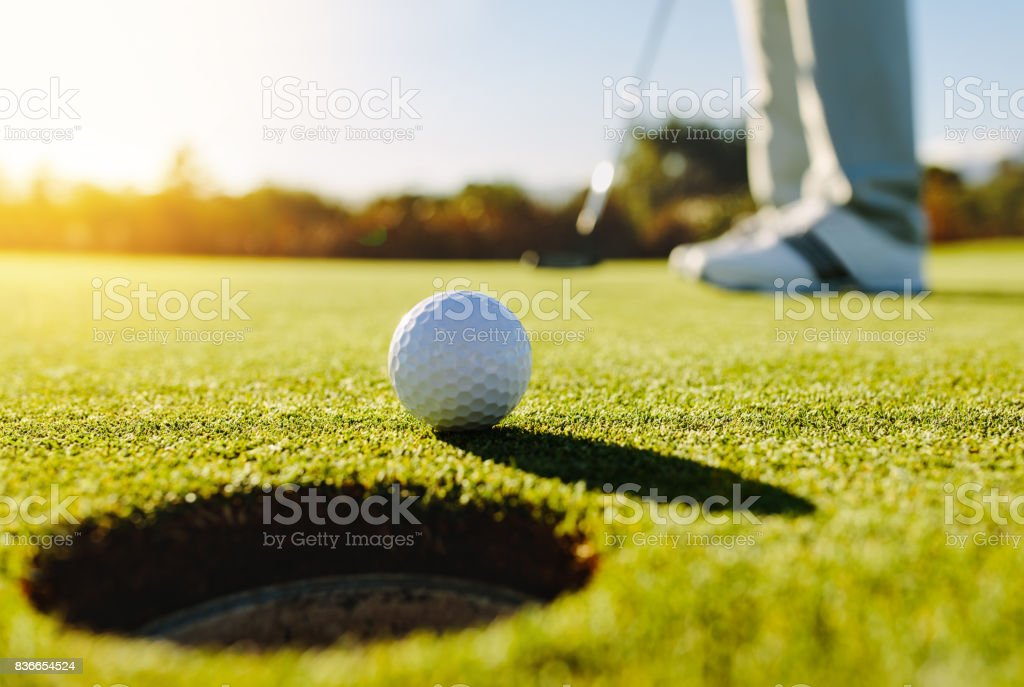 Professional golfer putting ball stock photo