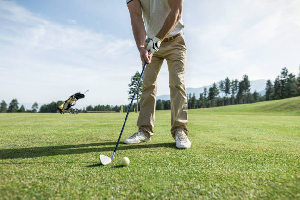 Professional golfer taking a tee shot on the golf course stock photo