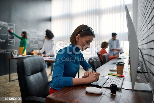 1134879628 istock photo Professional graphic designer. Side view of young creative woman using digital graphics tablet while sitting at her workplace in the creative agency. Web designer is drawing on tablet with pen stylus 1194380199