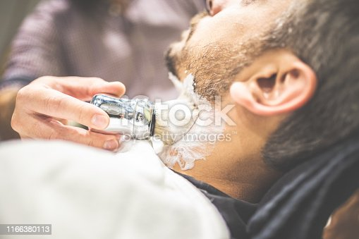 483333652 istock photo Professional hairdresser applying shaving foam on client skin in barbershop. 1166380113
