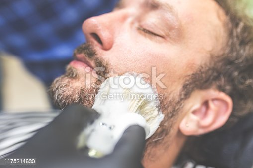 483333652 istock photo Professional hairdresser applying shaving foam on client skin in barbershop. 1175214630