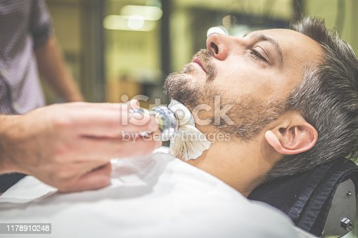 483333652 istock photo Professional hairdresser applying shaving foam on client skin in barbershop. 1178910248