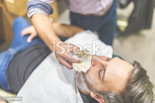 483333652 istock photo Professional hairdresser applying shaving foam on client skin in barbershop. 1178988902