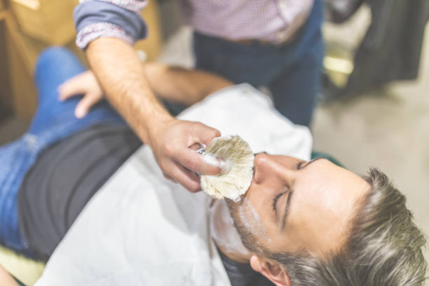 Professional hairdresser applying shaving foam on client skin in barbershop. Fashionable man client during beard shaving in barber shop. shaving brush shaving cream razor old fashioned stock pictures, royalty-free photos & images