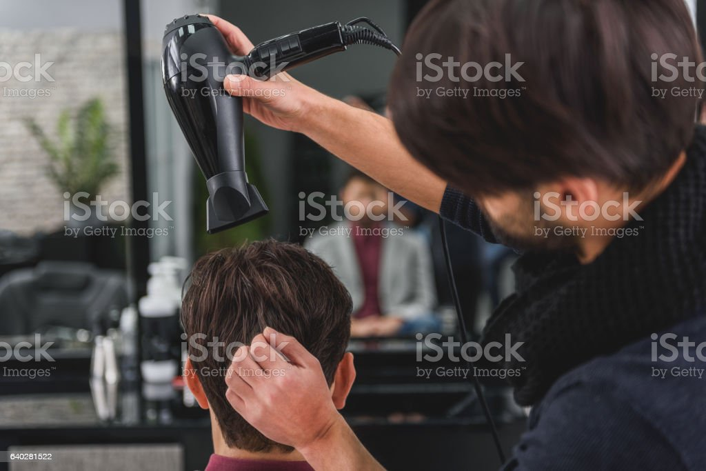 Professional hairdresser making human head dry stock photo