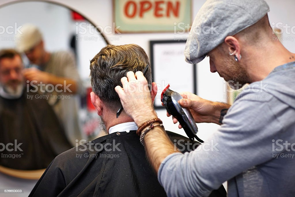 Professional hairdresser trimming client's hair stock photo