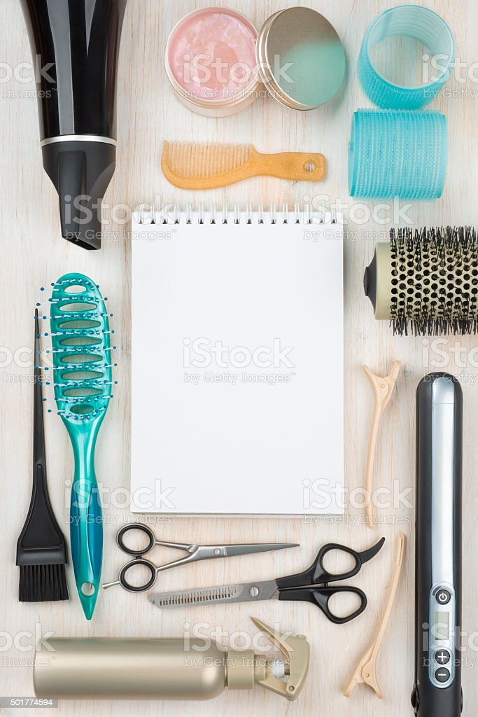Professional hairdressing tools and accessories with blank notebook in center stock photo